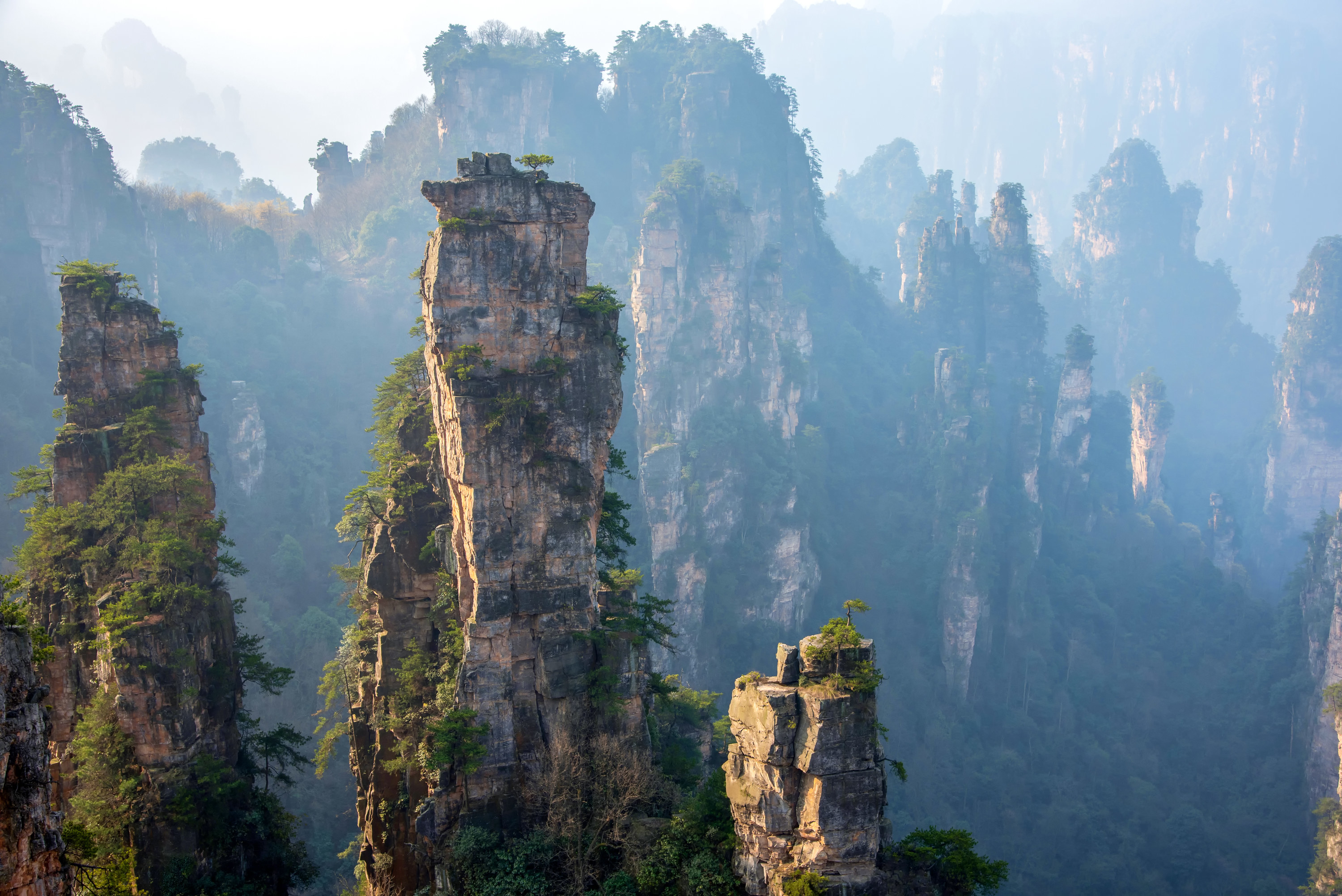 Tall pillar rock formations jutting out of a canyon with a cloudy fog in the background