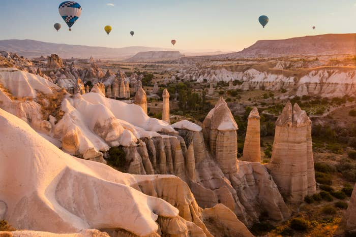 Goreme fairy chimneys. Tall pillared rock formations with hot air balloons floating overhead.