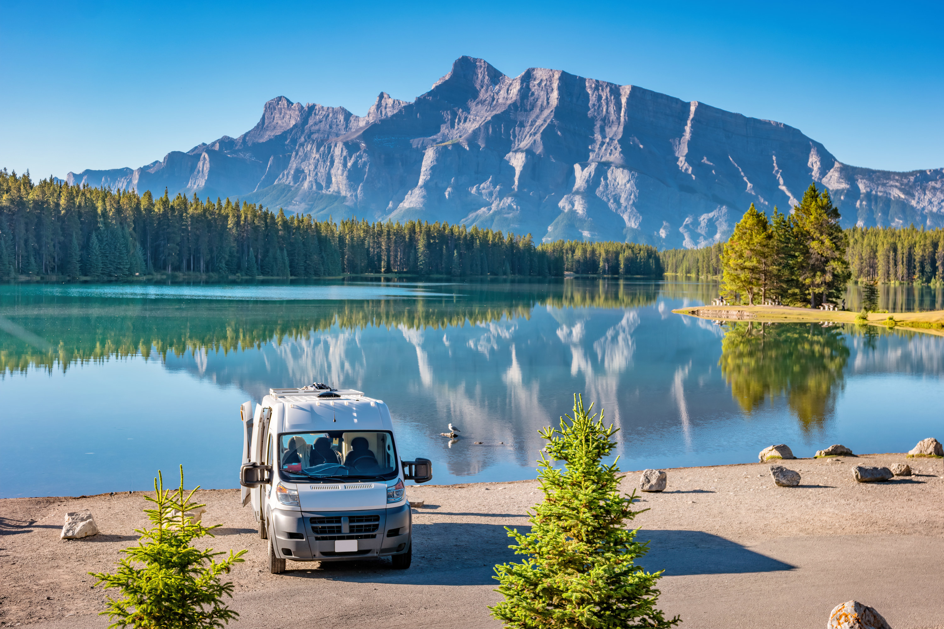 Campervan parked on a lake with tall trees and mountain behind it