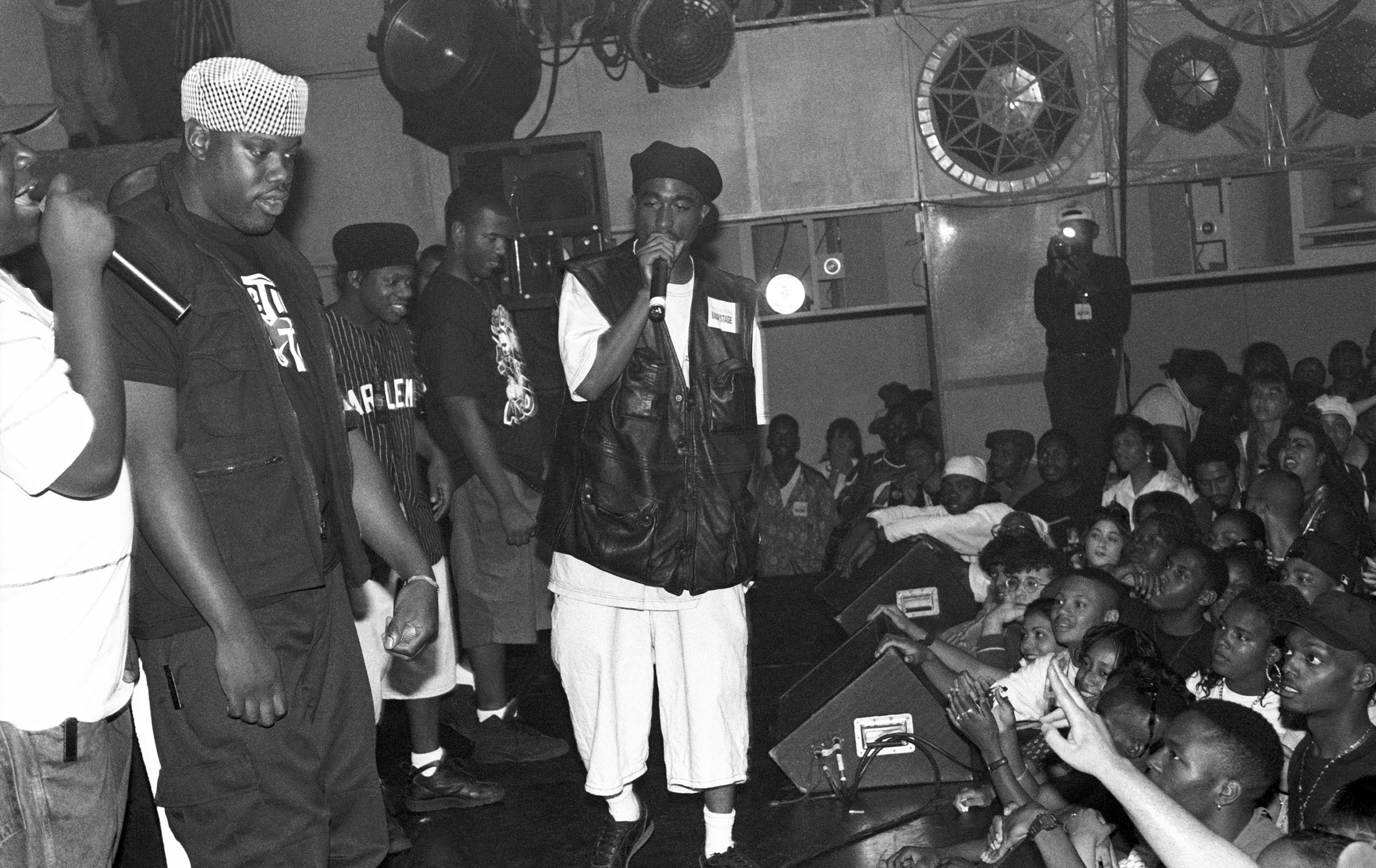 Tupac on a stage with other people raps into a microphone above a crowd of fans