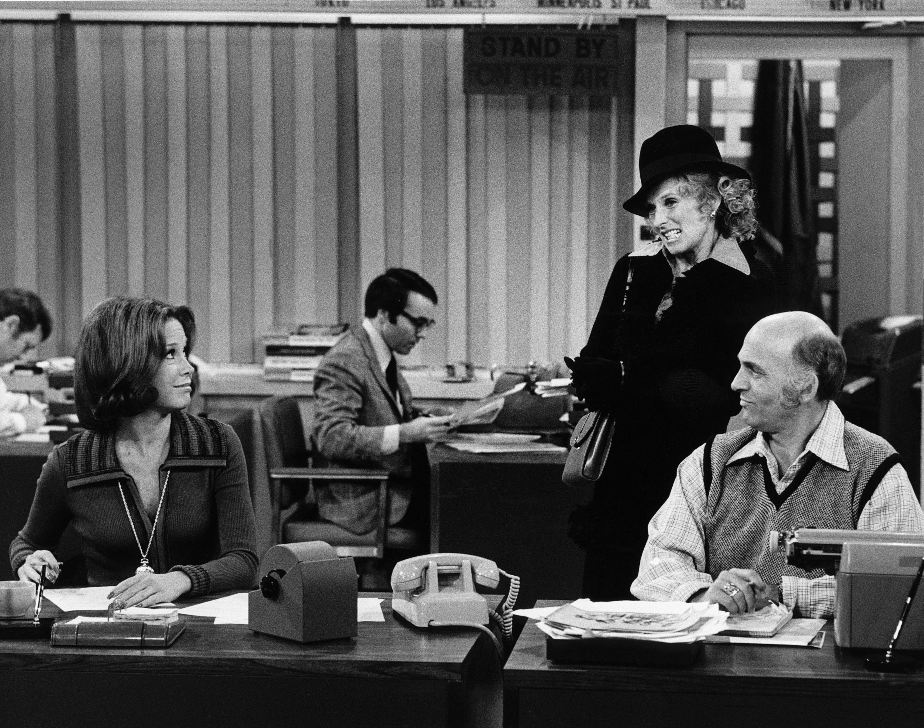 Mary Tyler Moore and Gavin MacLeod sit at a desk while Cloris Leachman stands behind them