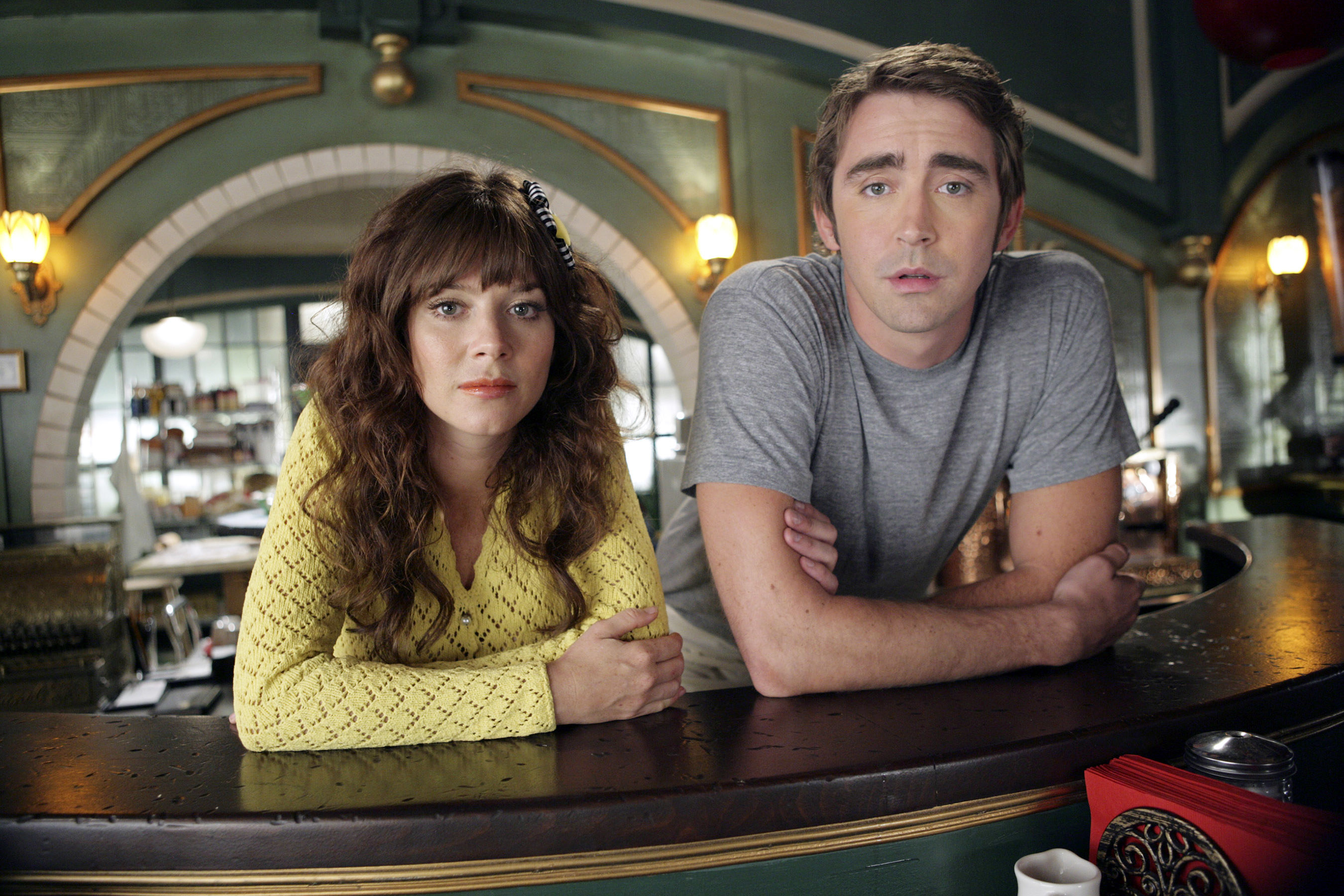 Anna Friel and Lee Pace lean on the diner counter