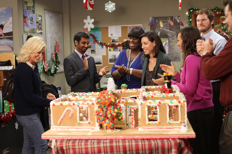 Amy Poehler, Aziz Ansari Retta, Aubrey Plaza, Rashida Jones, Chris Pratt, and Nick Offerman stand around a giant gingerbread house.