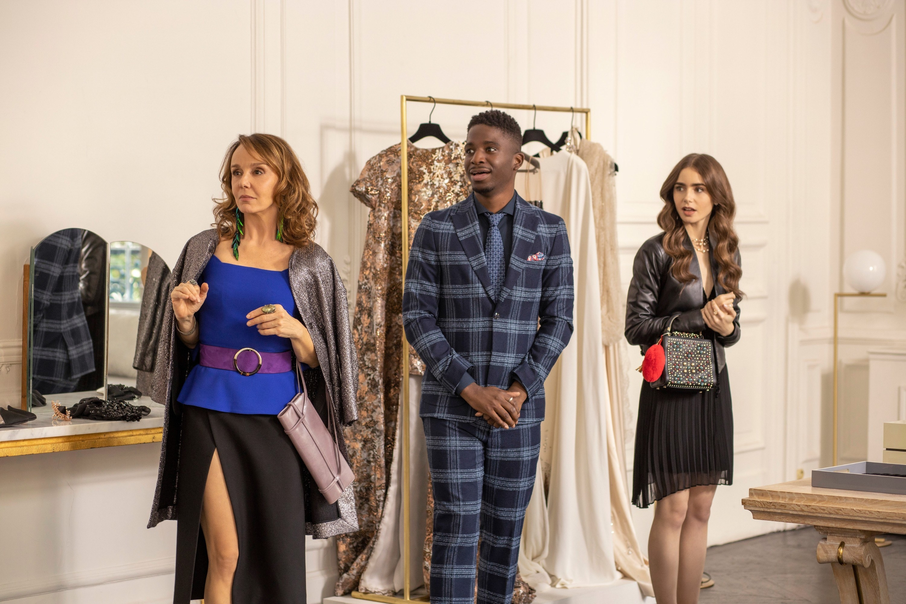Philippine Leroy-Beaulieu, Samuel Arnold, and Lily Collins stand in a fashion show room