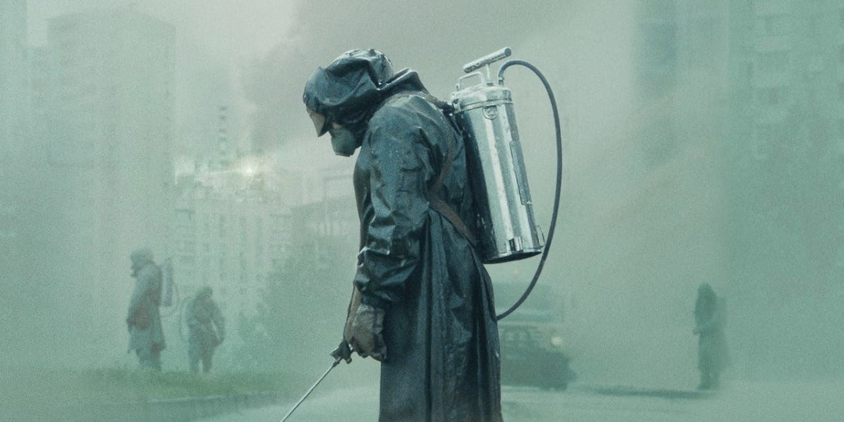 A man in a hazmat suit sprays liquid from a canister on his back