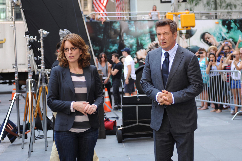 Tina Fey and Alec Baldwin stand outdoors on set