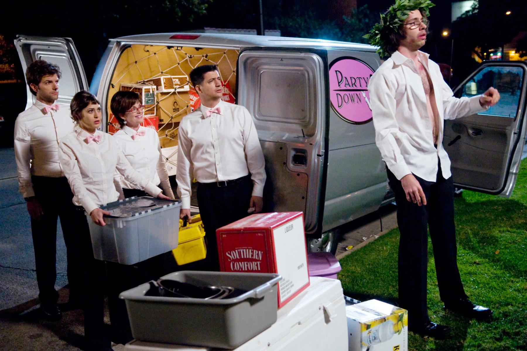 Adam Scott, Lizzy Caplan, Megan Mullally, Ken Marino, and Martin Starr stand outside a catering truck.