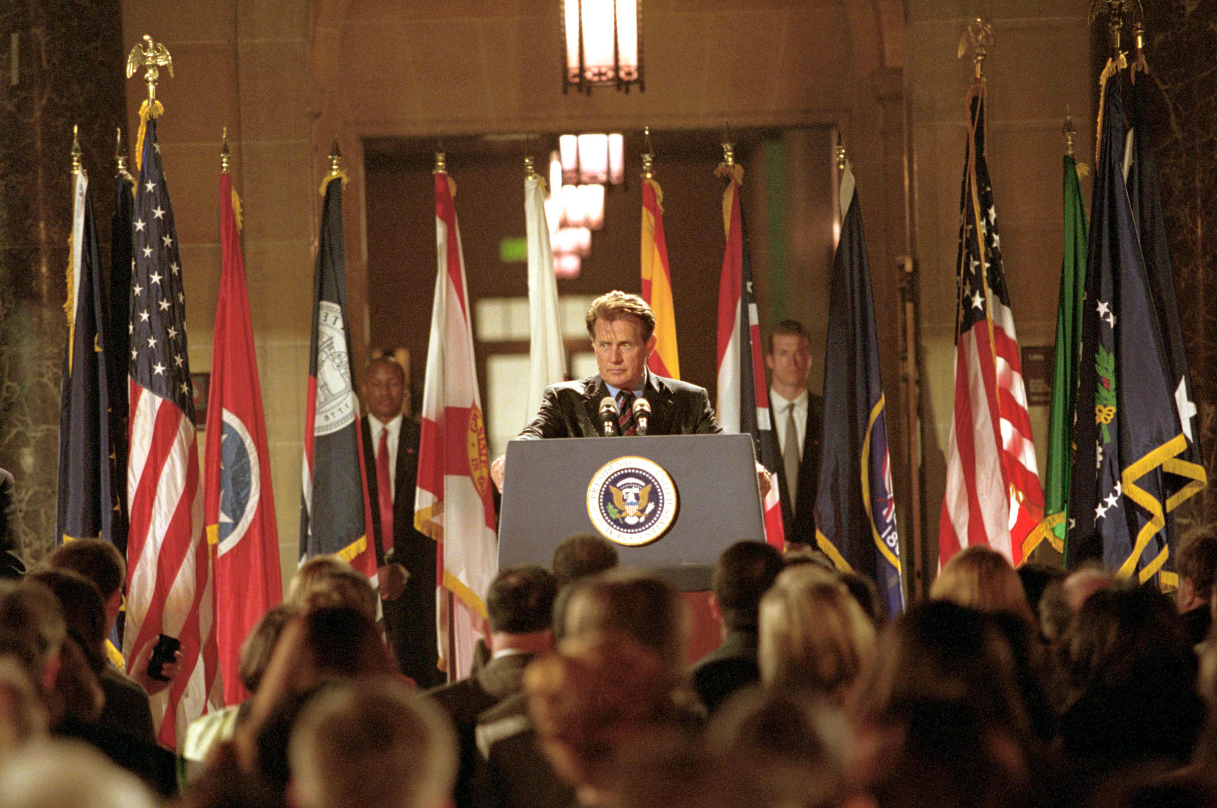 Martin Sheen gives a speech from a podium with the US seal on the front