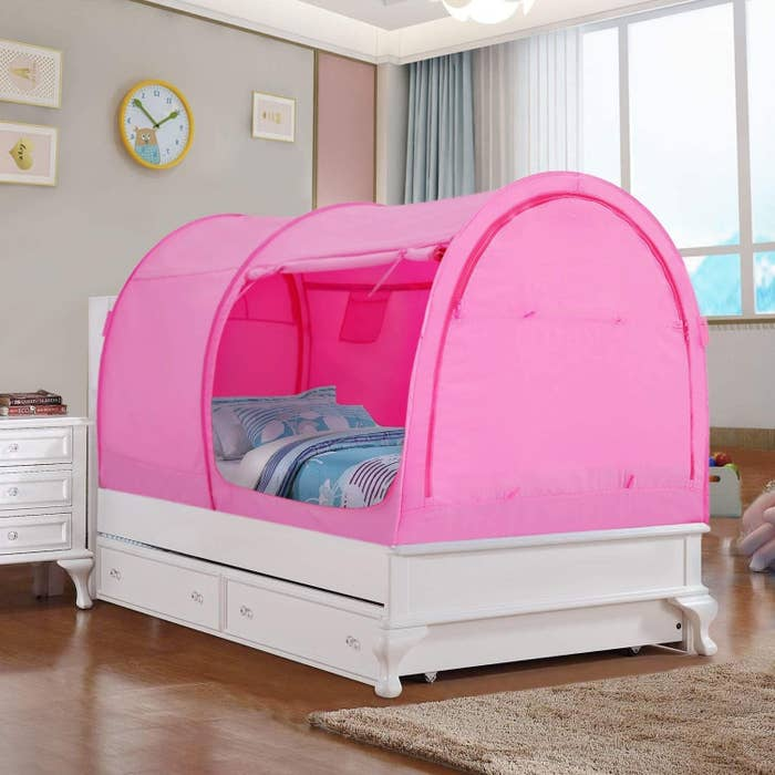 the pink bed tent over a twin bed with an unzipped entrance