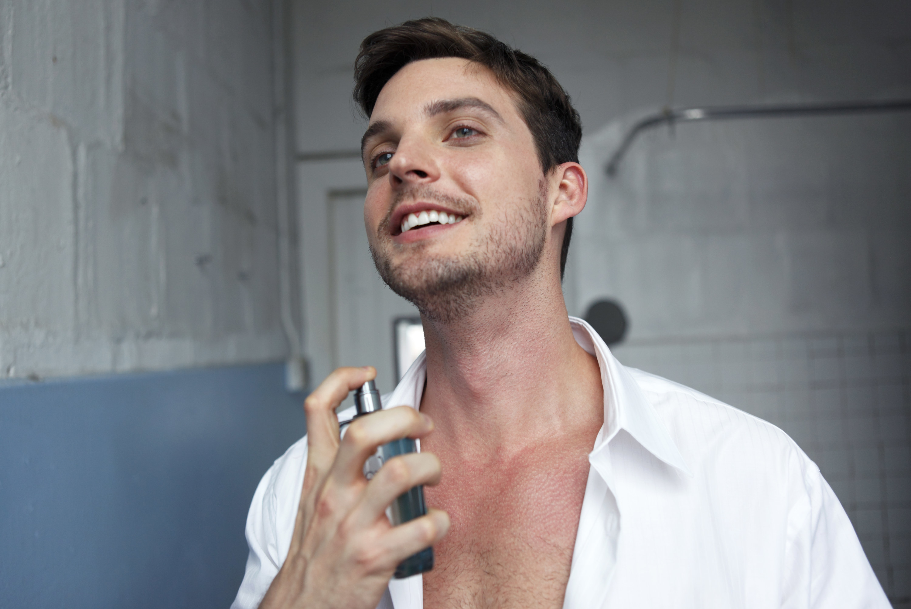 A man spraying cologne on himself