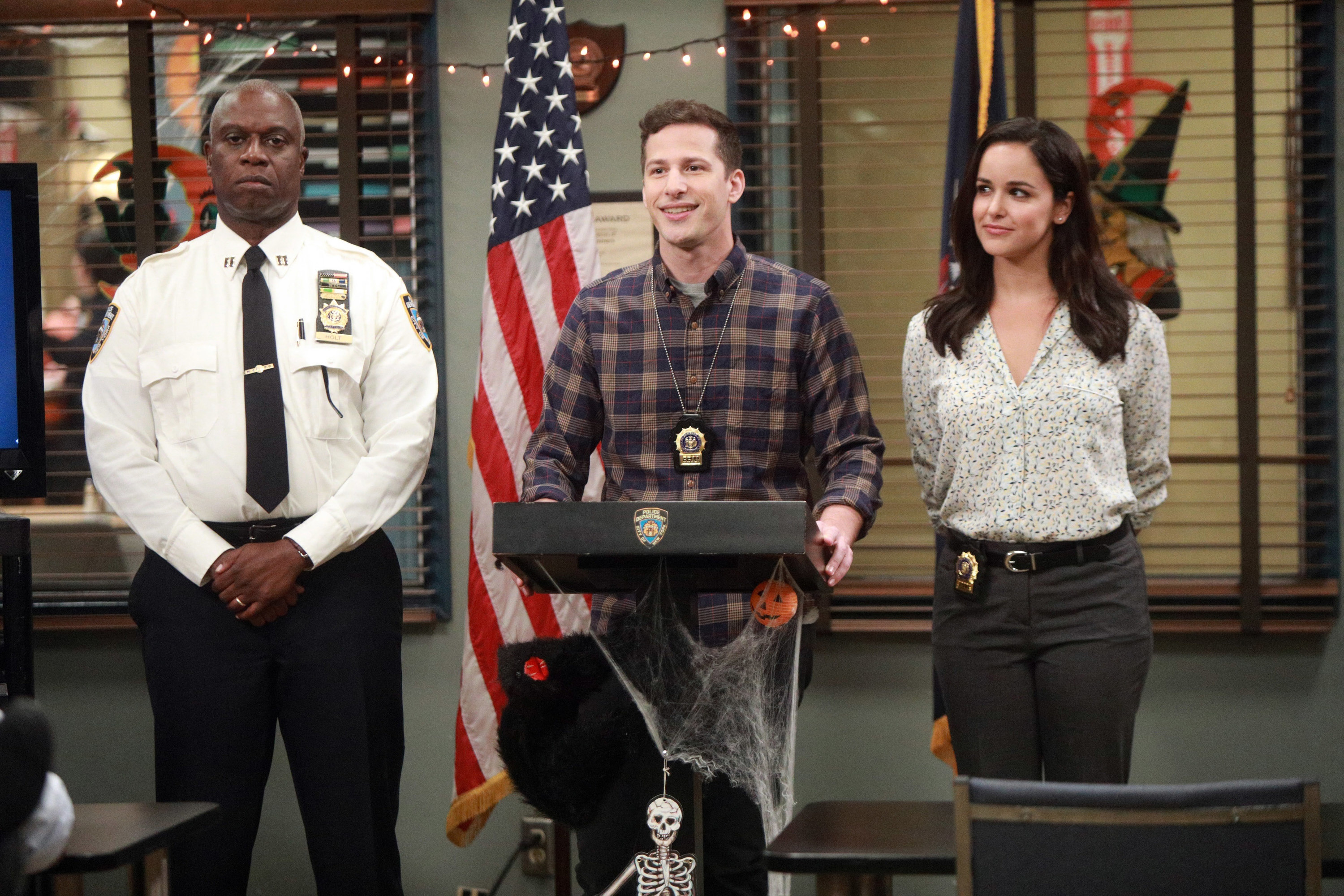 Andre Braugher, Andy Samberg, and Melissa Fumero deliver a speach at the front of the precinct