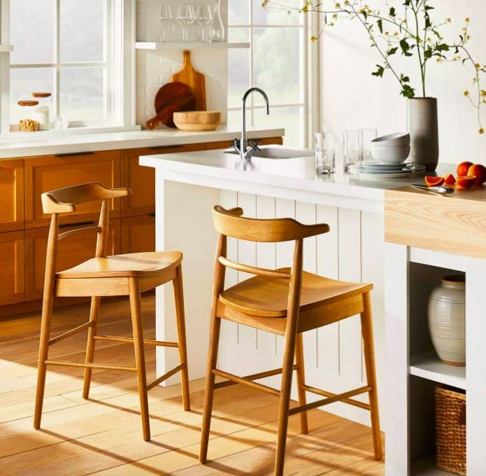 Two wood barstools by a white kitchen island.