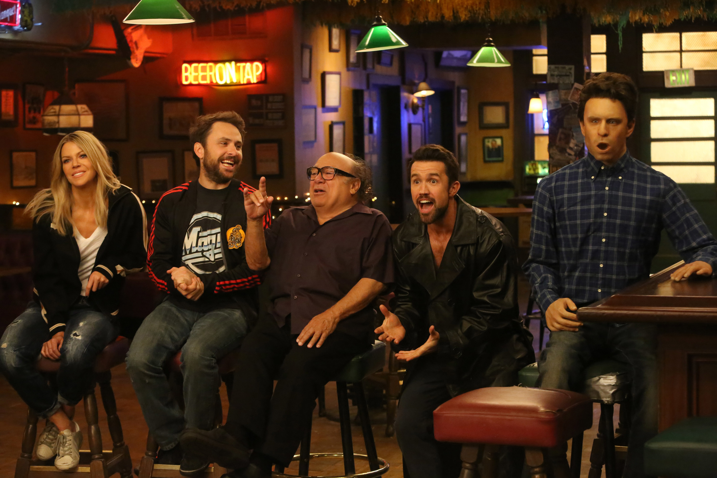 Kaitlin Olson, Charlie Day, Danny DeVito, Rob McElhenney, and a sex doll that looks like Glenn Howerton sit in Paddy's Pub