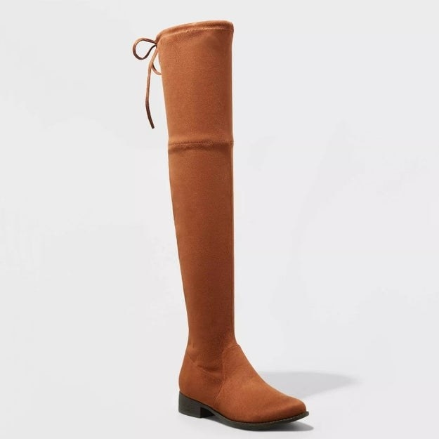 Camel colored boots with black sole, tie string detail at the top of the boot
