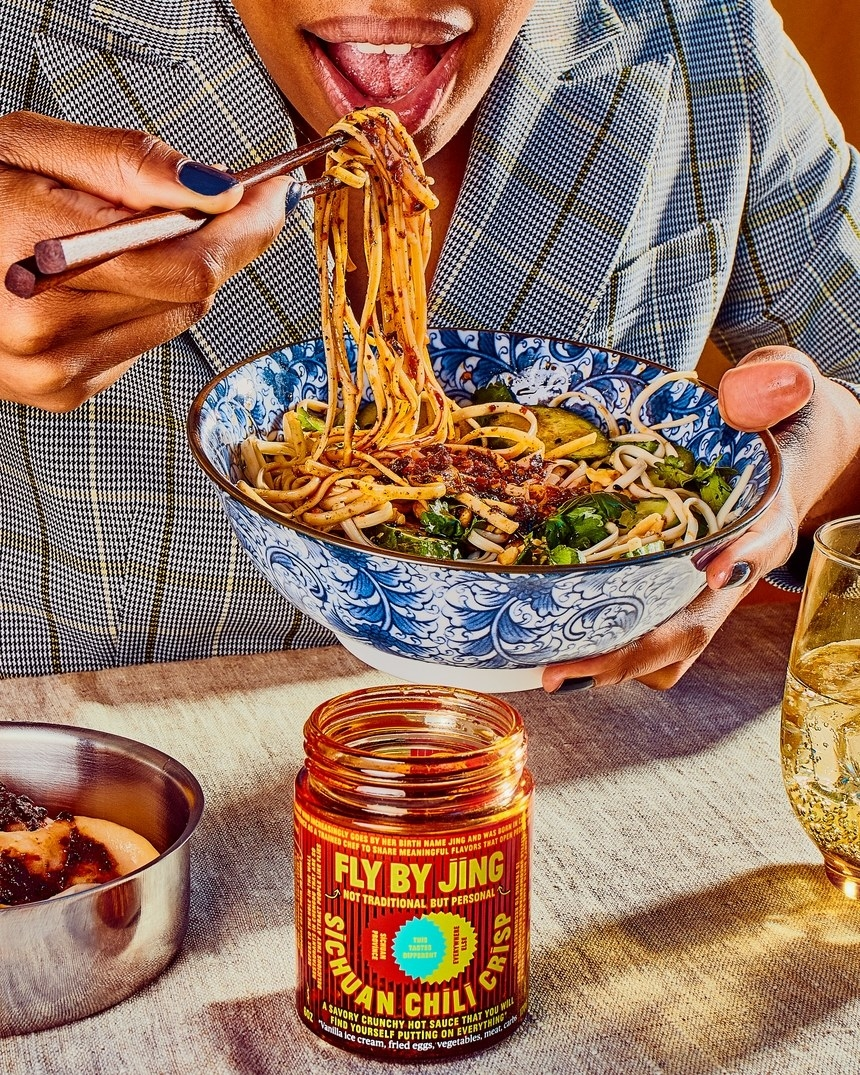 The jar of sauce in front of a model eating a bowl of noodles