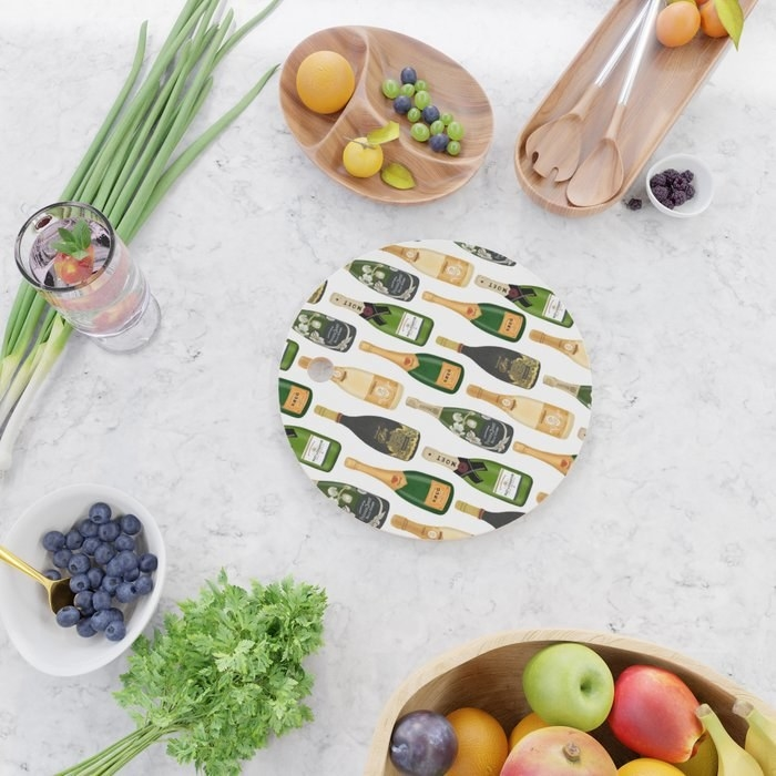 The round cutting board with a repeat pattern of different styles of champagne bottles