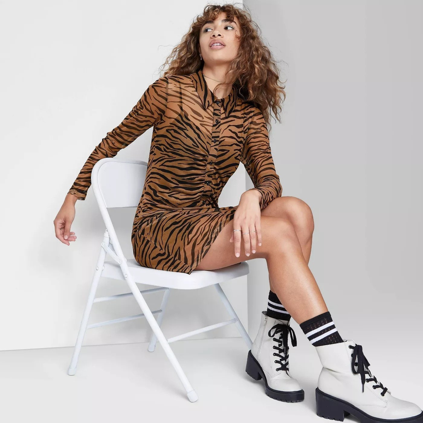 Model wearing brown and black tiger print shirt dress, stops pasts the thigh