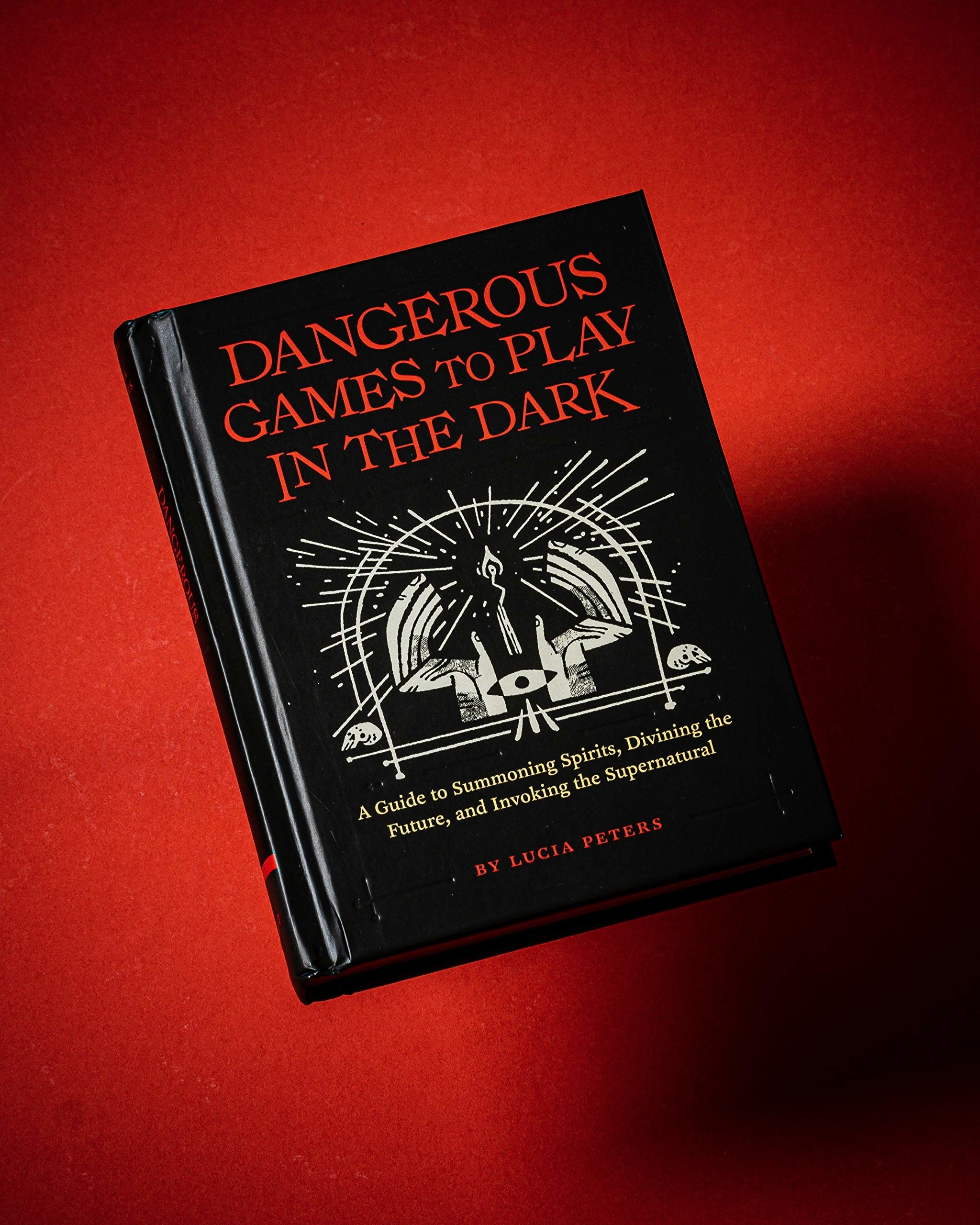 The book against a red and shadowy back drop