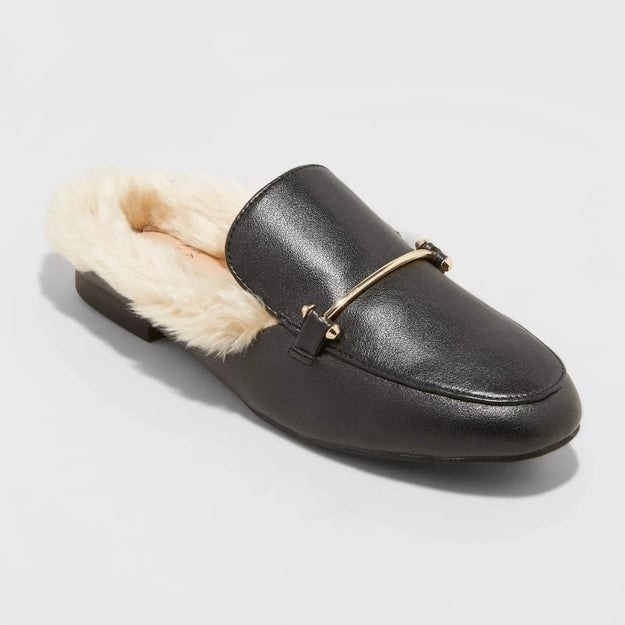 Black mule with gold accent, off-white fur around the back of the shoe