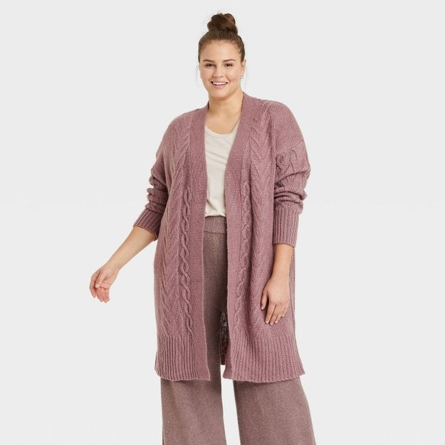 Model wearing dark mauve cardigan, withs sweater texture, goes past the thigh