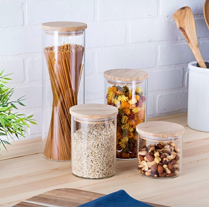Four canisters filled with oats, pasta and nuts sitting on a kitchen countertop.