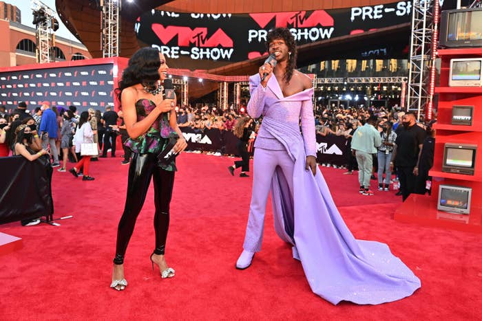 Lil Nas X wearing a suit-gown hybrid and a wavy wig