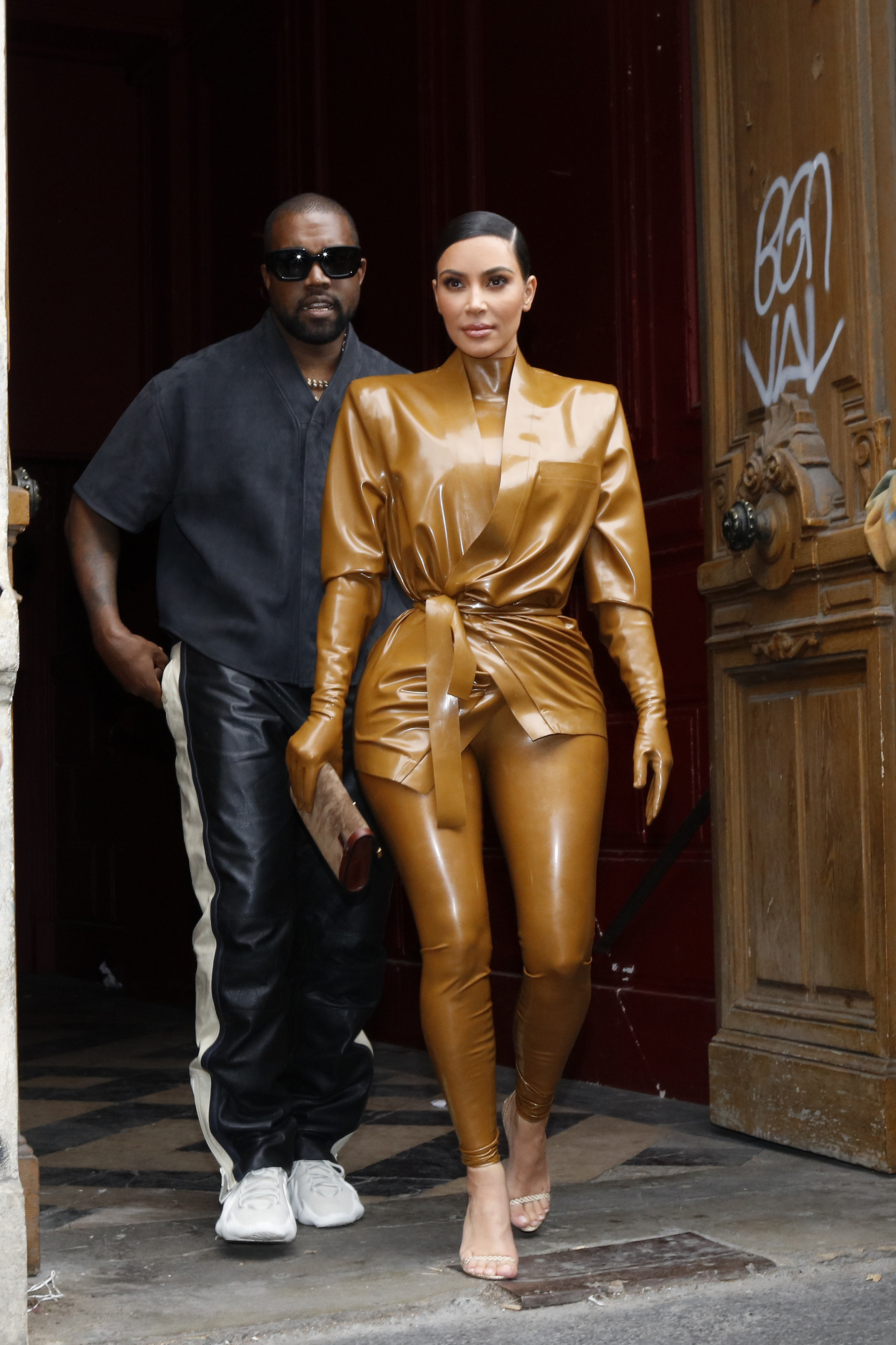 Kanye on the left and Kim, wearing a latex bodysuit with gloves, walking out of a building together