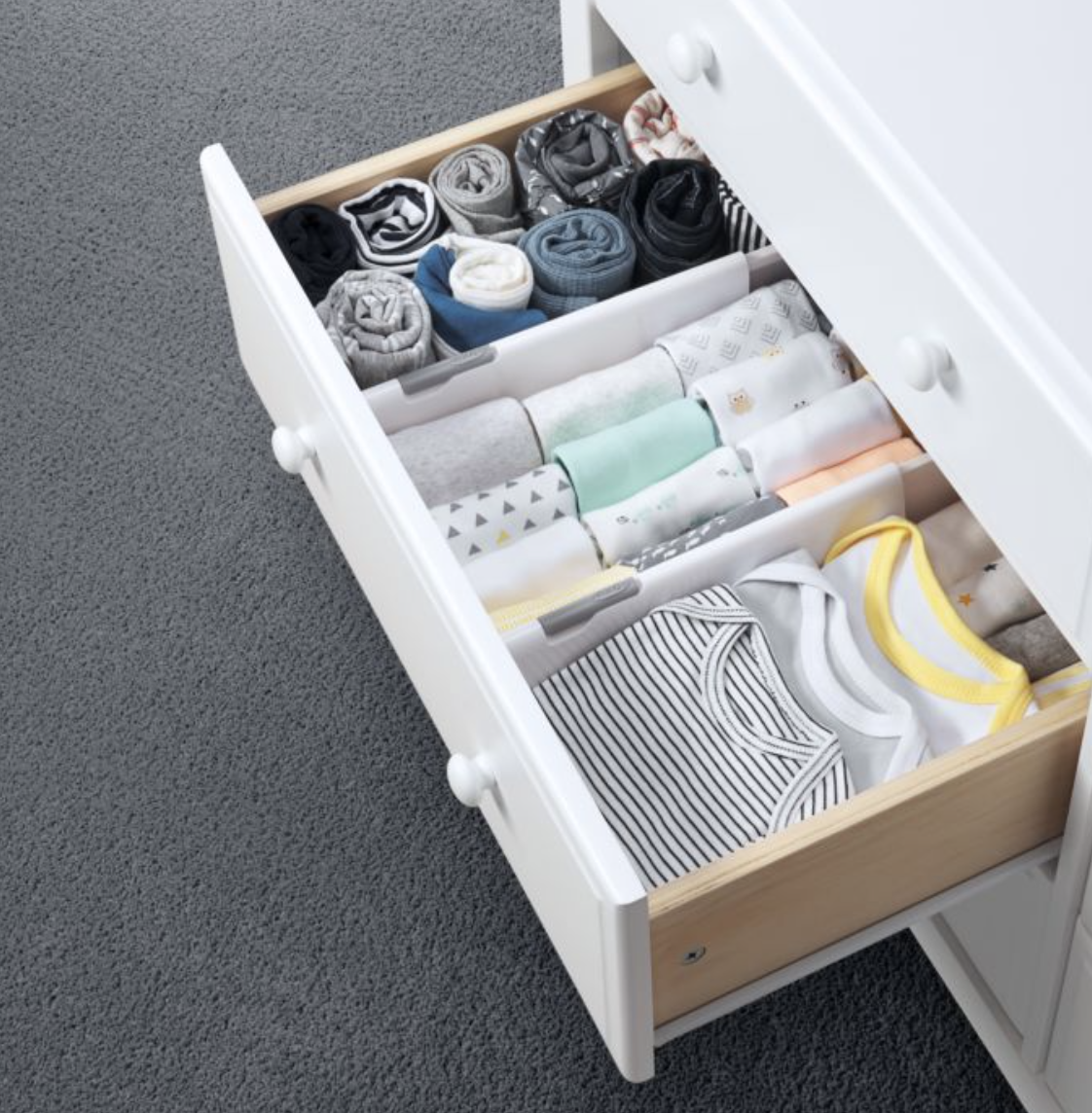 a drawer with dividers in it separating baby clothing