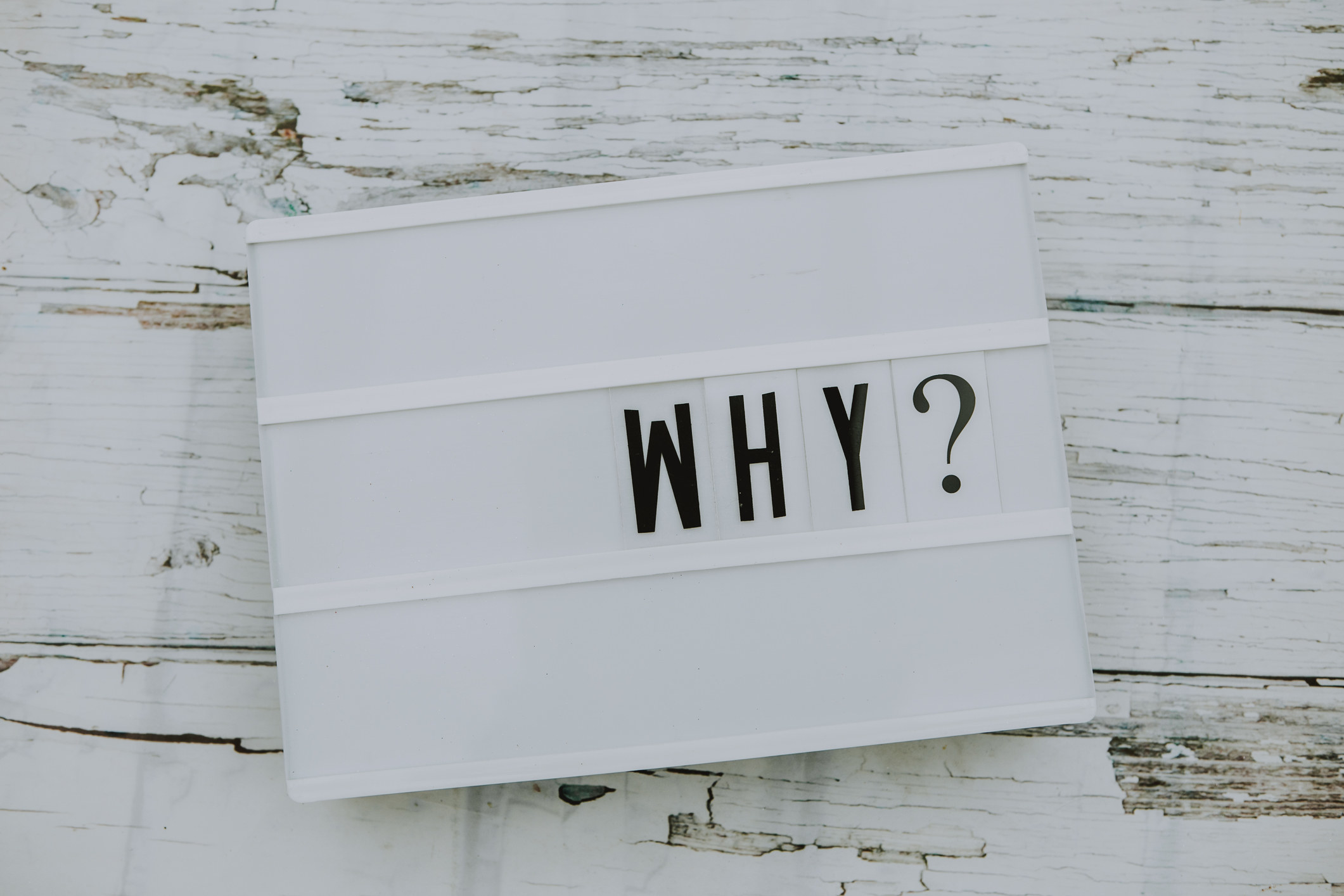 """A stock image of letters on a bulletin board spelling out, """"Why?"""""""