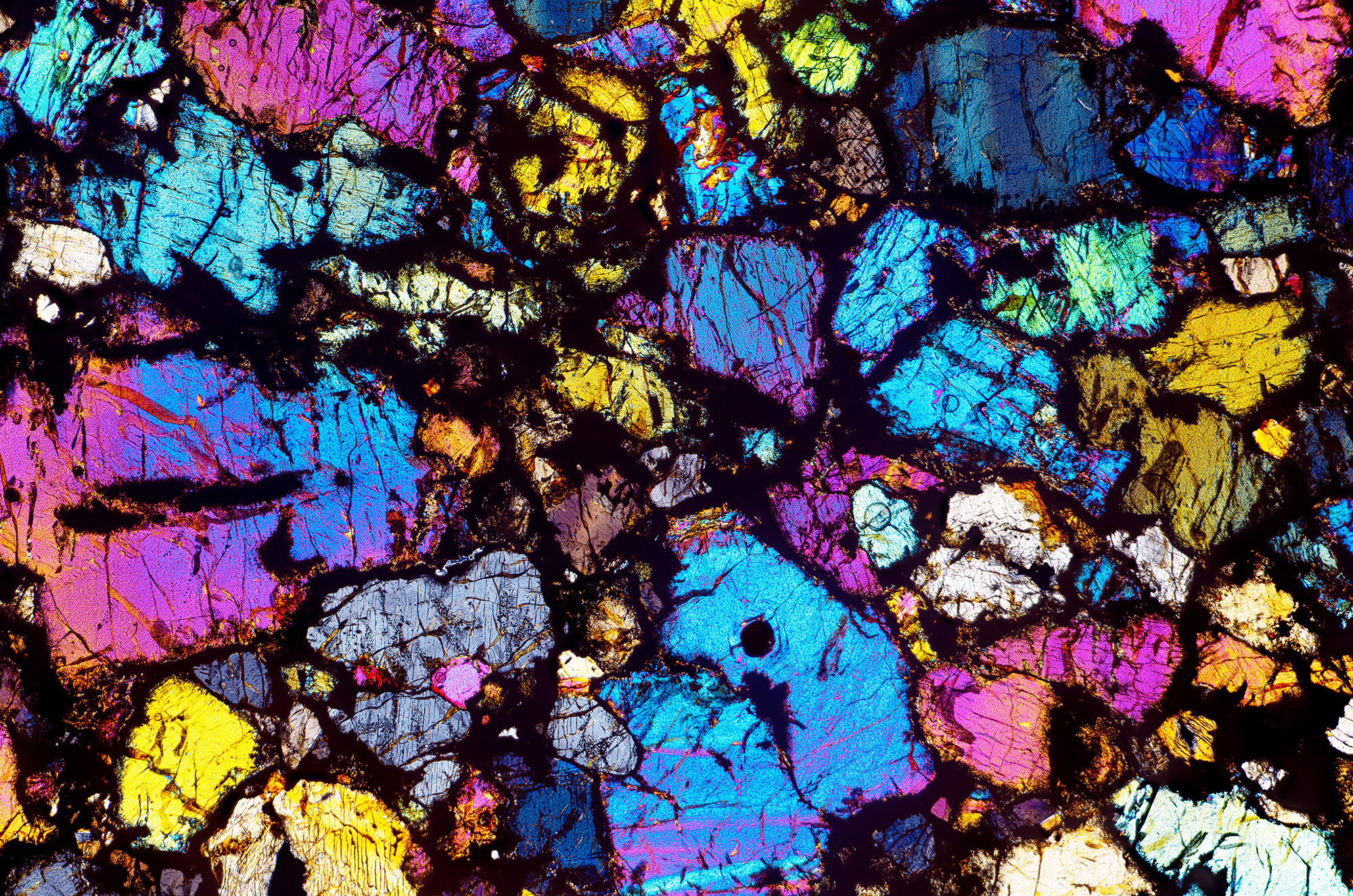 A jumble of colors on black with rocks and streaks of color throughout,  magnified many times