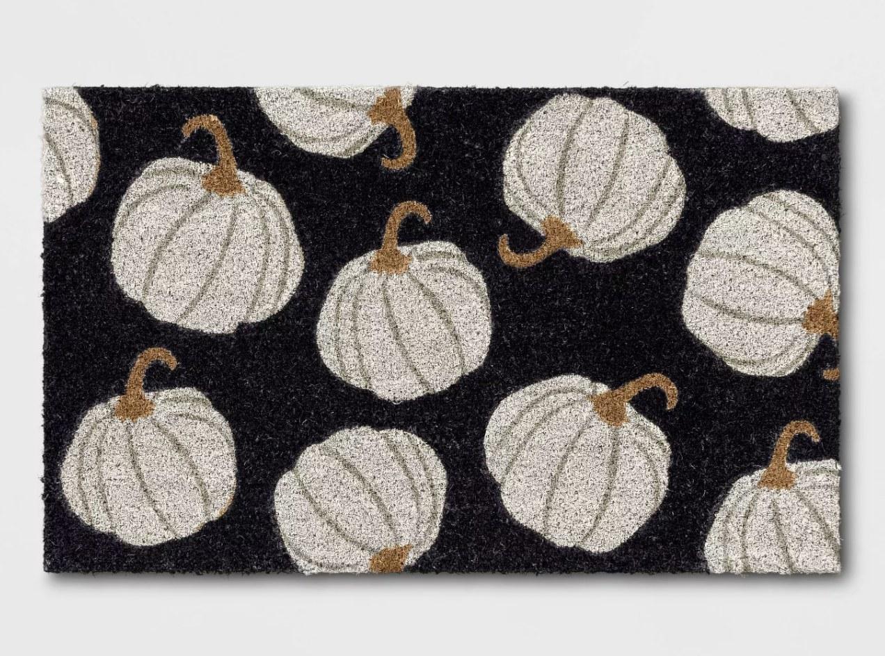 a black doormat with grey pumpkins on them