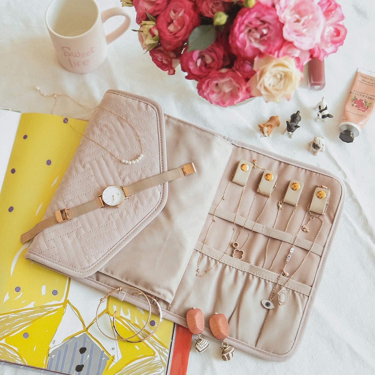 The light pink  fabric case laid out flat with jewelry secured in it