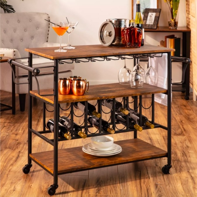 Bar cart filled with bottles, glasses and accessories.