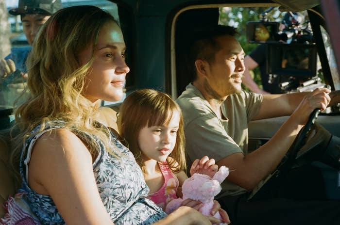 The family sitting inside a pickup truck, smiling