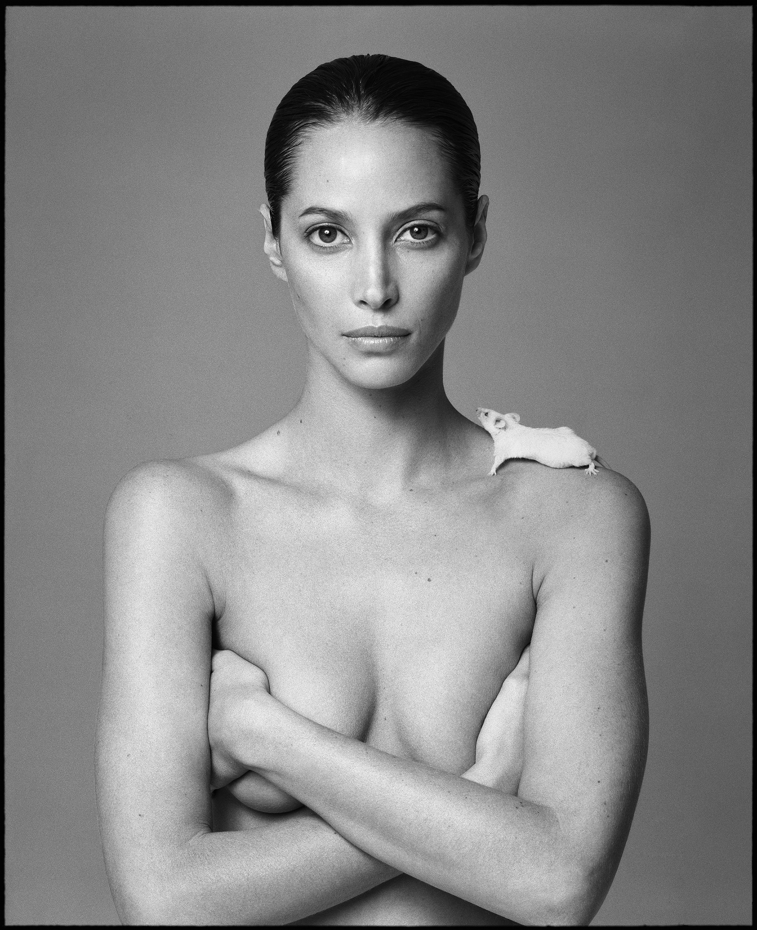 Christy Turlington naked with her arms crossed and a mouse on her shoulder, looking at the camera