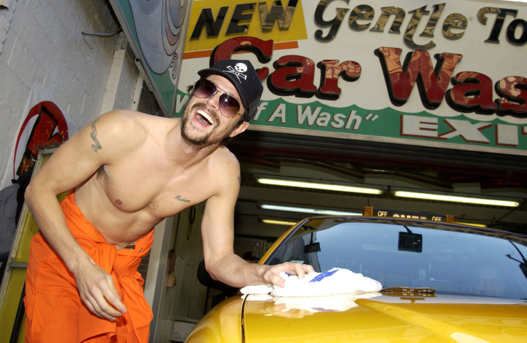 Knoxville in an orange jumpsuit washing a car