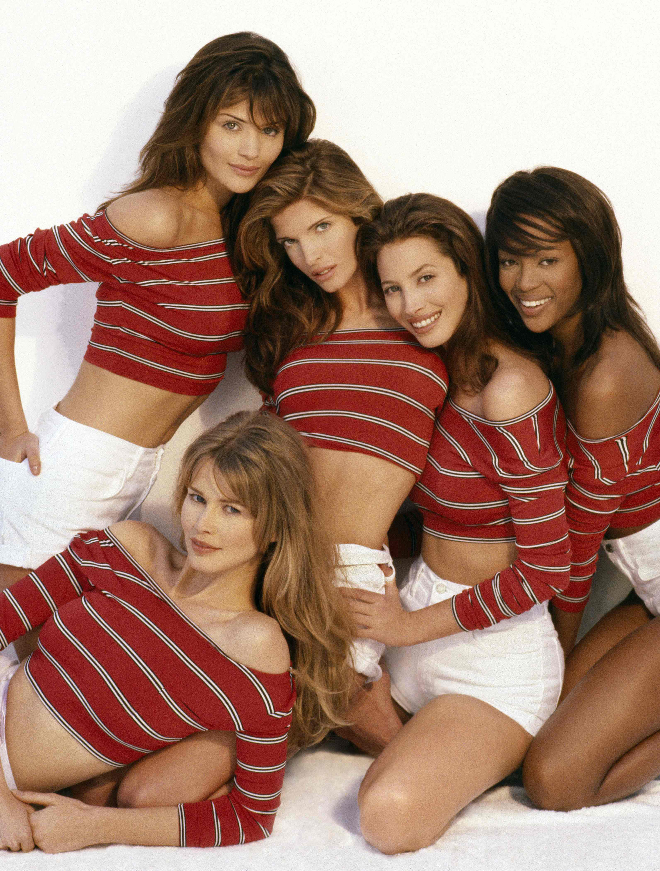 Helena Christensen, Claudia Schiffer, Stephanie Seymour, Christy Turlington, Naomi Campbell in striped shirts and shorts on a plush rug, looking at the camera