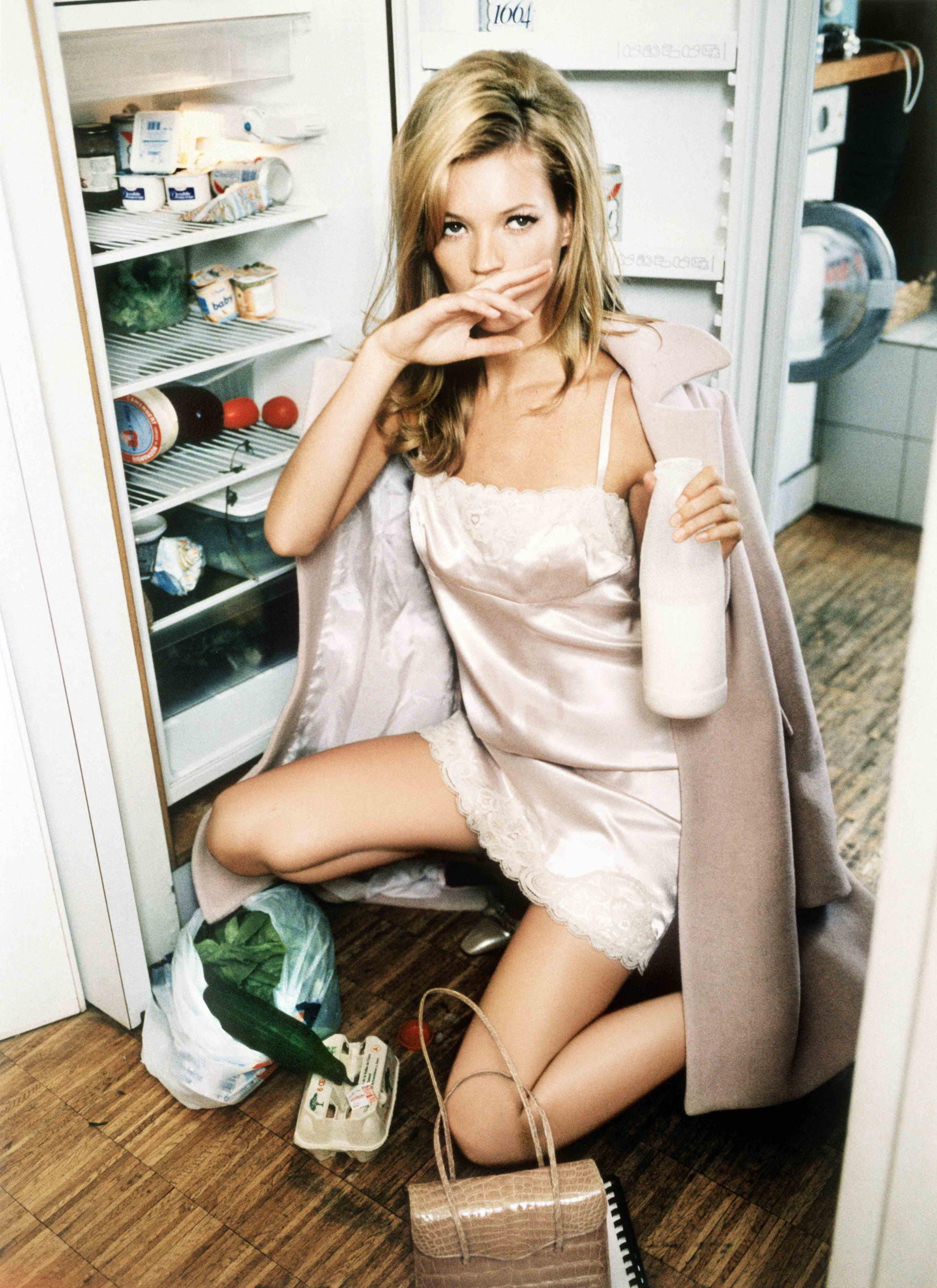 Kate Moss in a slip dress and coat in front of an open refrigerator with groceries on the ground, drinking milk