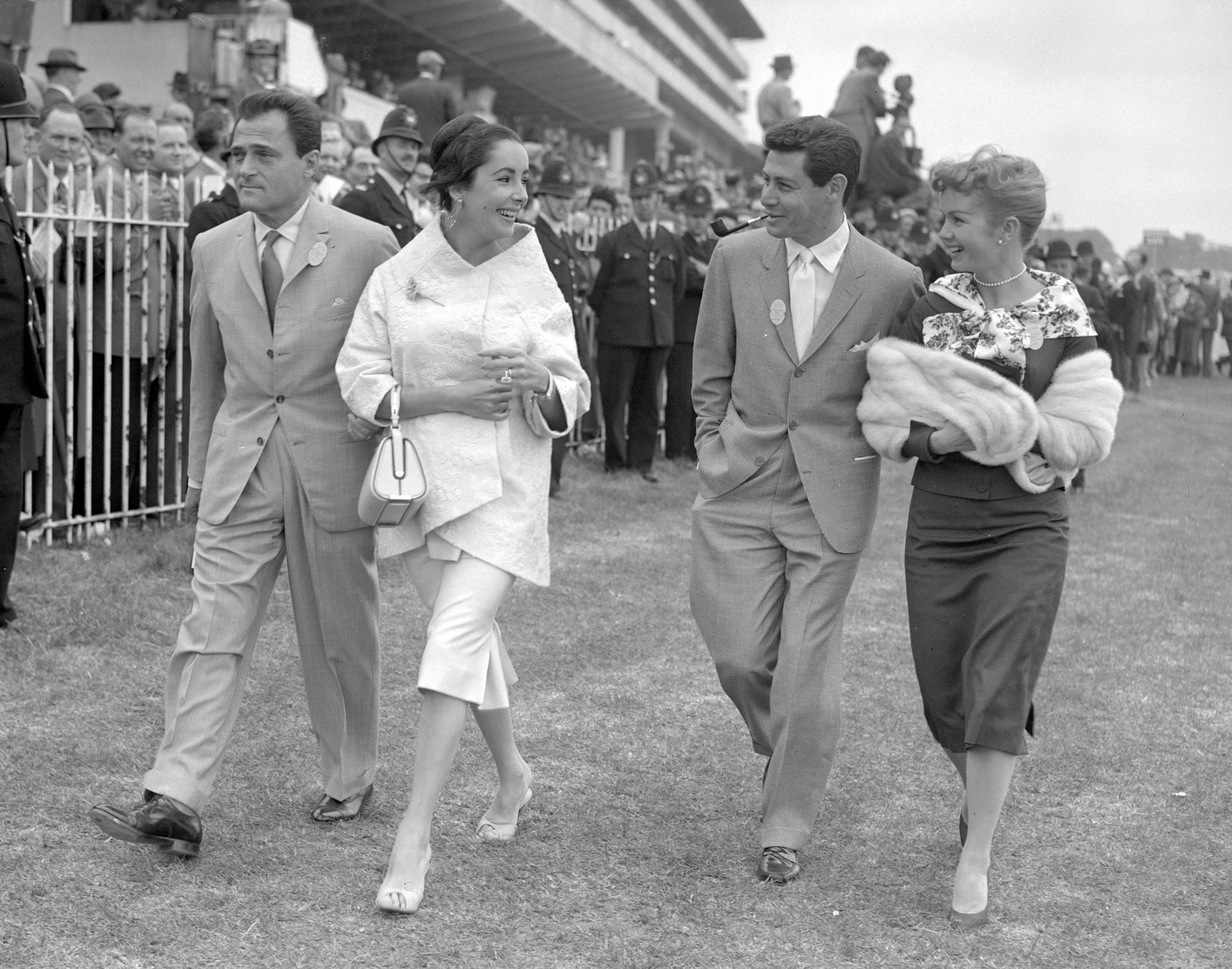 the two couples stroll together at a horse derby