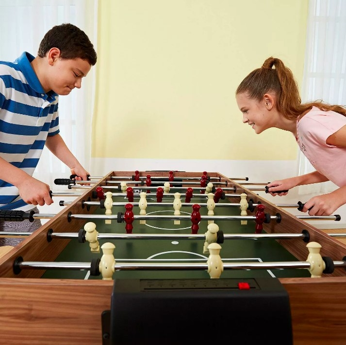 Two kids playing a game of foosball