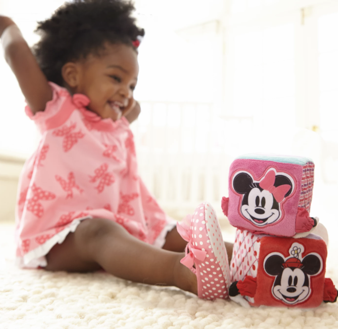 a baby playing with the soft blocks with minnie mouse on them