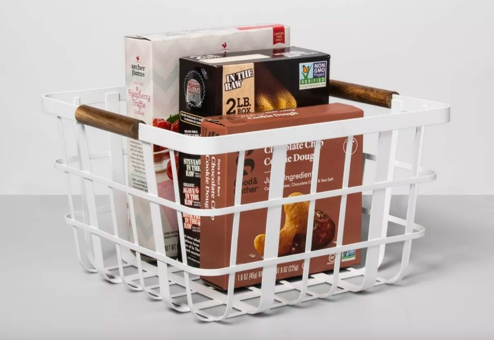 White metal basket filled with packaged foods.