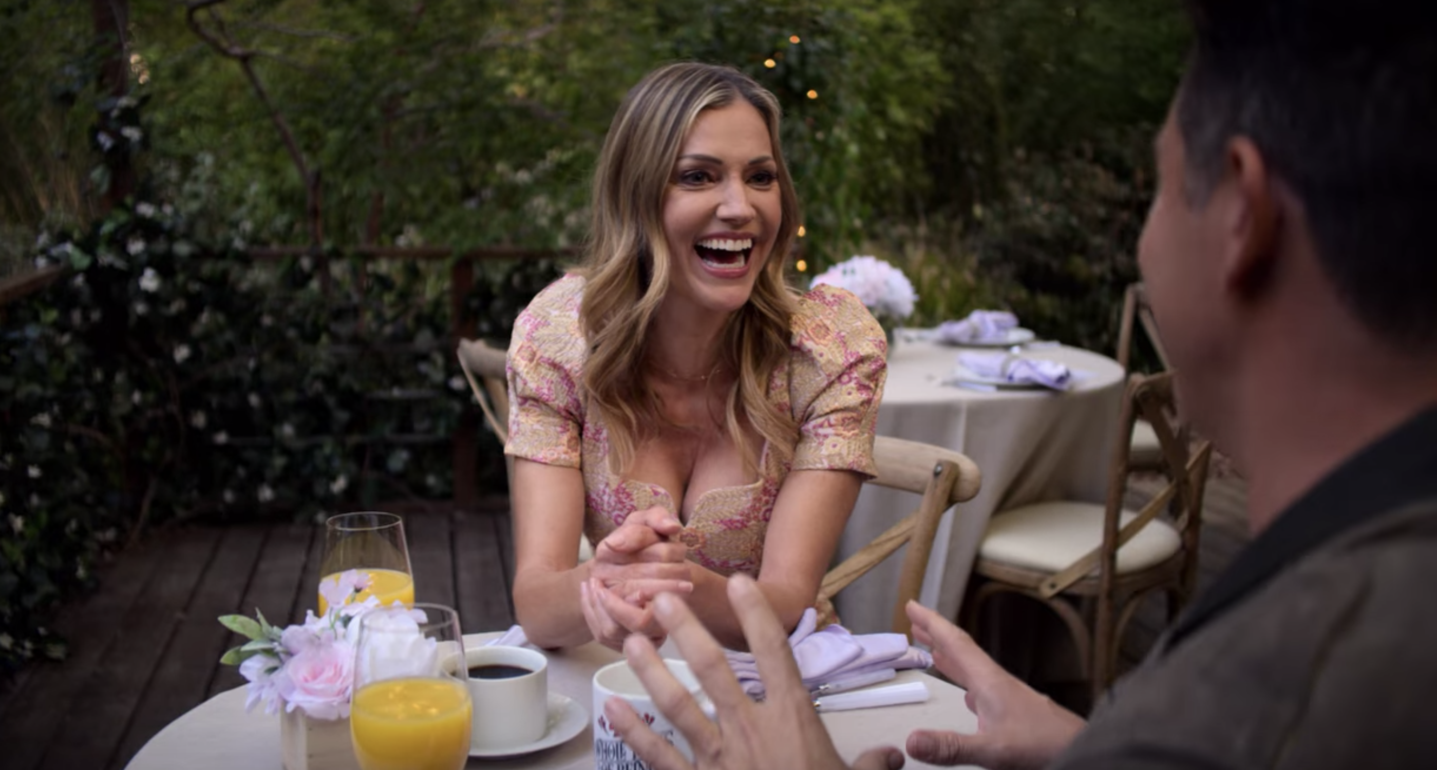 Tricia and Kevin at a restaurant with coffee and orange juice during a scene