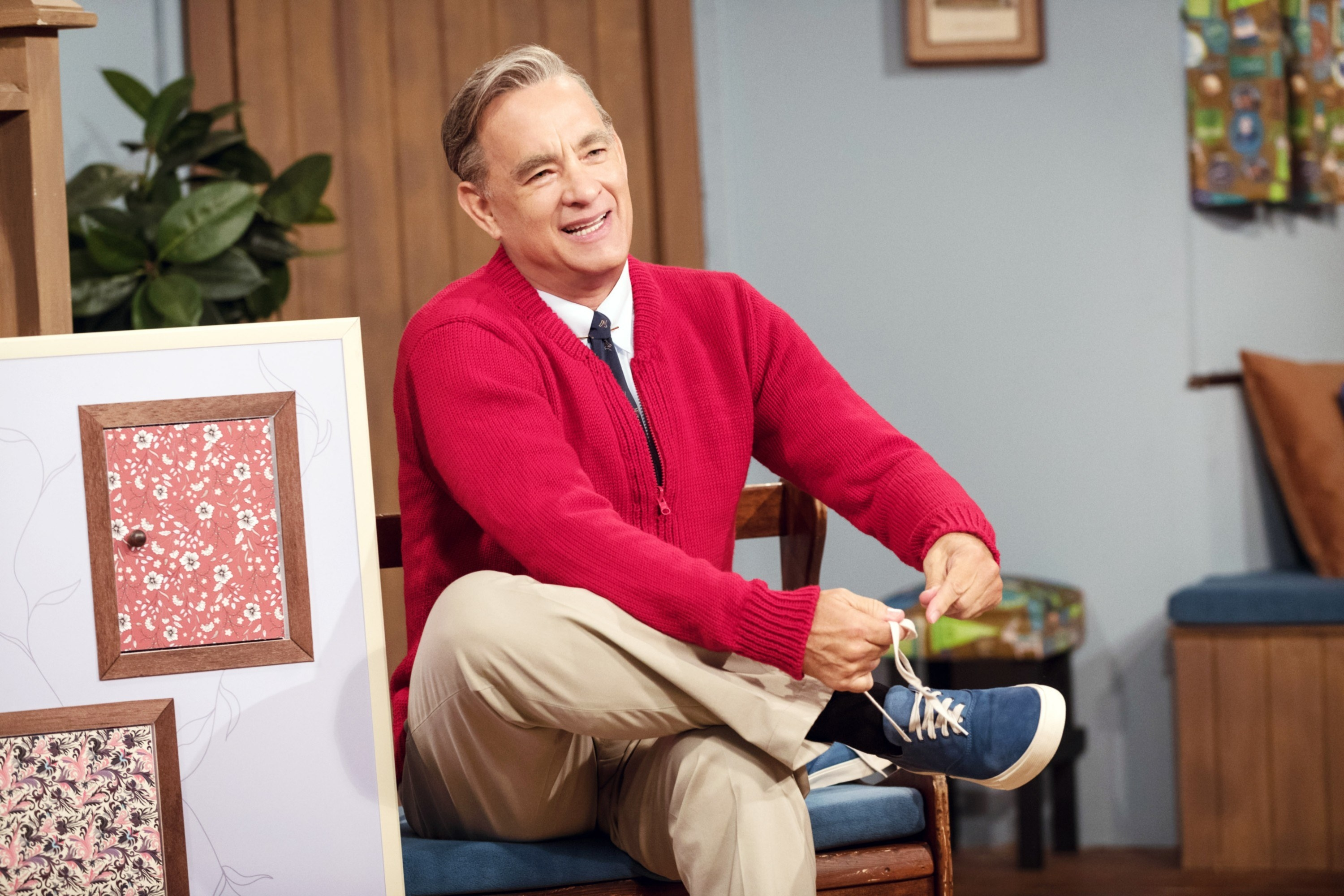 Fred Rogers dressed in sneakers, pants, a shirt and tie, and a sweater