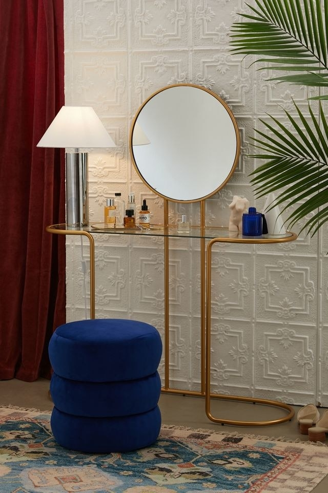 the gold vanity which has a circular mirror
