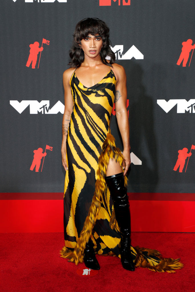 Bretman Rock wearing the dress on the red carpet with thigh high boots and a curly wig