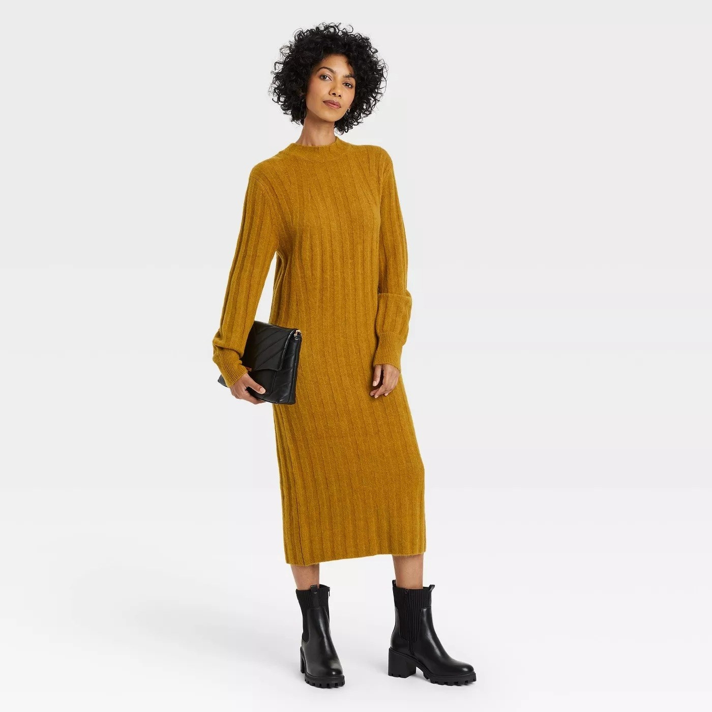 Model wearing mustard yellow dress, goes past the ankle