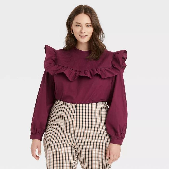 Model wearing burgundy blouse