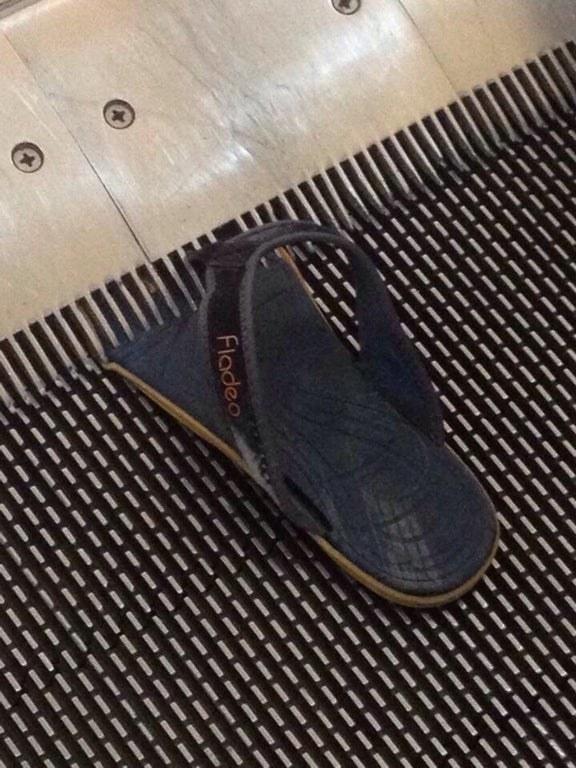 a flip flop sucked into an escalator