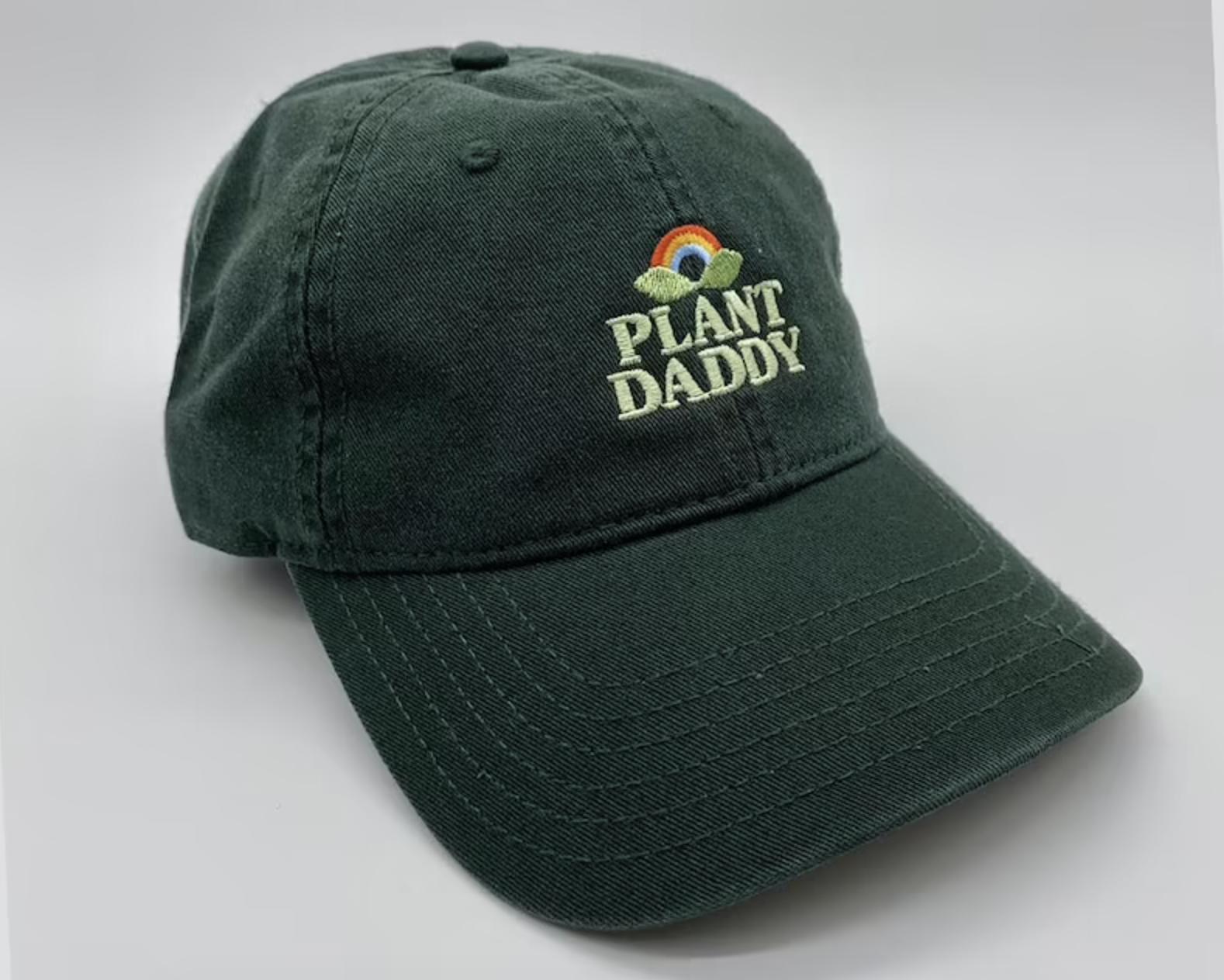 "A dark green hat says ""plant daddy"" on it"
